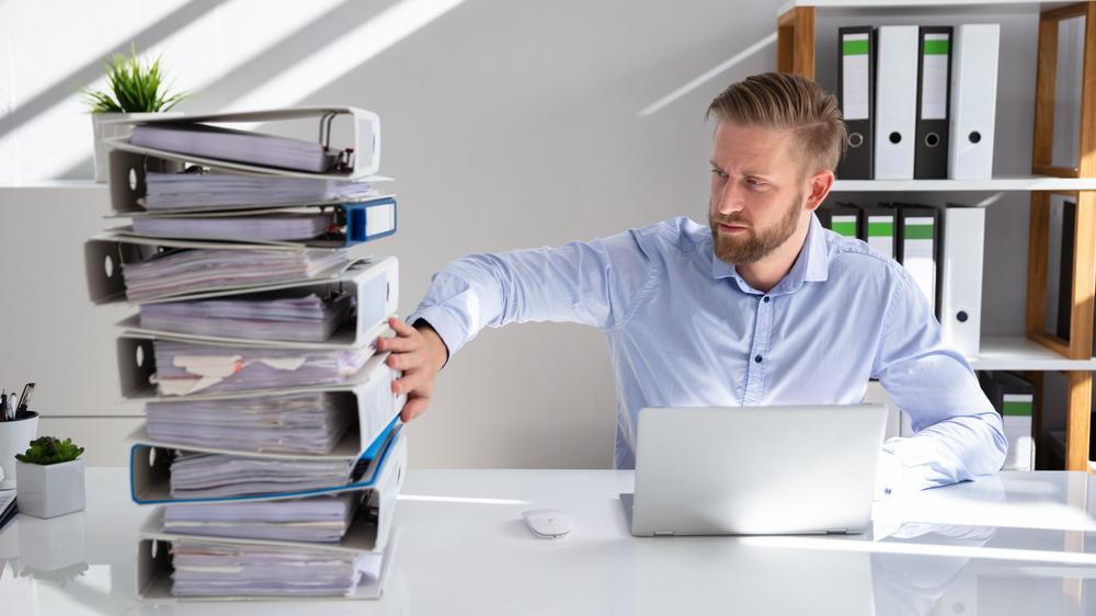 Tårn med permer og mann foran datamaskin